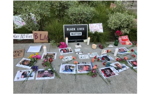 "Signs (""Black Lives Matter""), photos, candles and flowers laid out on sidewalk"