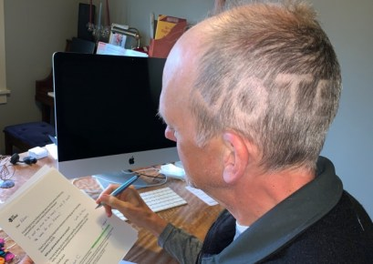 """Steve C sitting at a desk with """"VOTE"""" shaved into the left side of his head"""