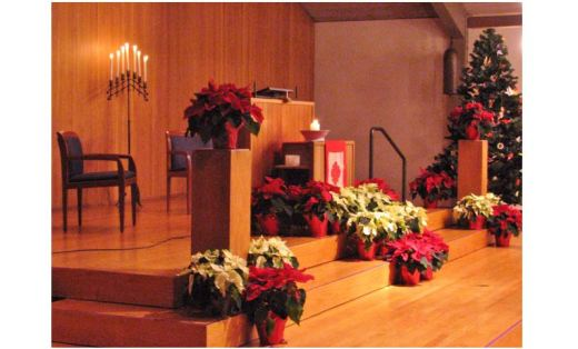 UUC chancel decorated with poinsettias, candles and a tree - 2014