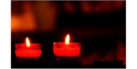 Two lit votive candles glowing orange against a dark background