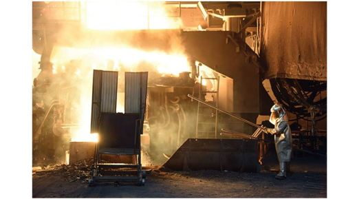 A steelworker in a protective suit checks the temperature of molten metal in furnace at the TMK Ipsco Koppel plant in Koppel, Pennsylvania on March 9, 2018.