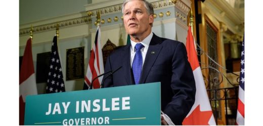 Governor Jay Inslee at podium with flags in the background
