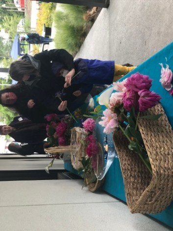 A line of people choosing flowers from baskets on an outside table