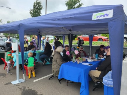 People of all ages sitting and standing under a blue canopy; flowers on the tables