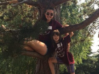 A Youth Counselor and Chalice Camp camper sit in a tree together and smile at the camera.