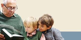 Grandfatherly man reading to two young children