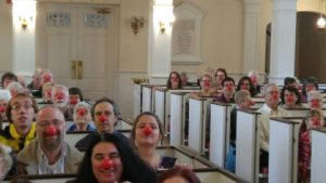 congregants seated in pews and wearing red noses