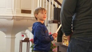 young boy lighting a candle in the church