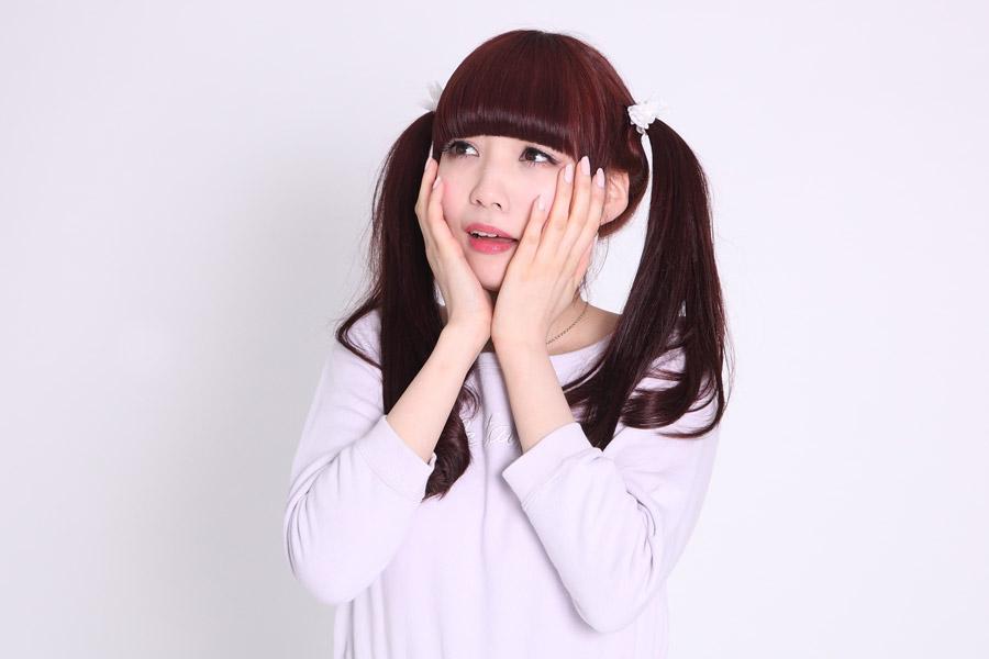 頬に手を当ててショックを受ける日本人女性