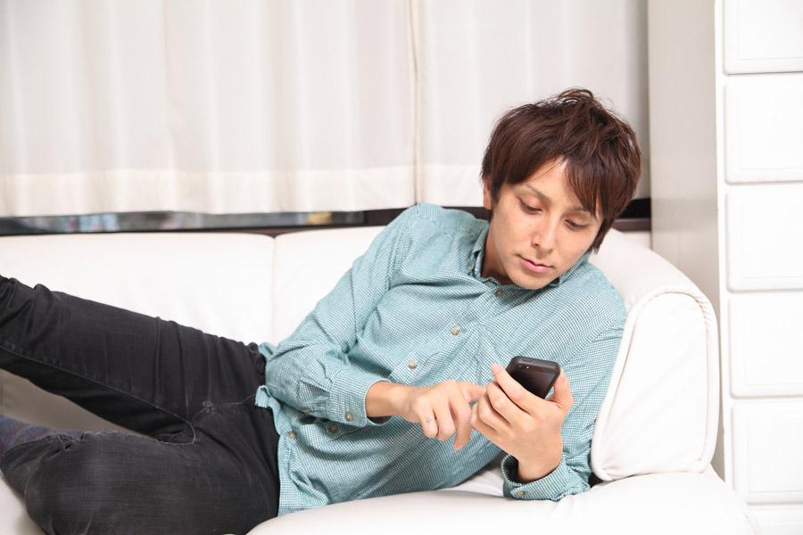 スマホを見ながらだらだらと過ごす日本人男性