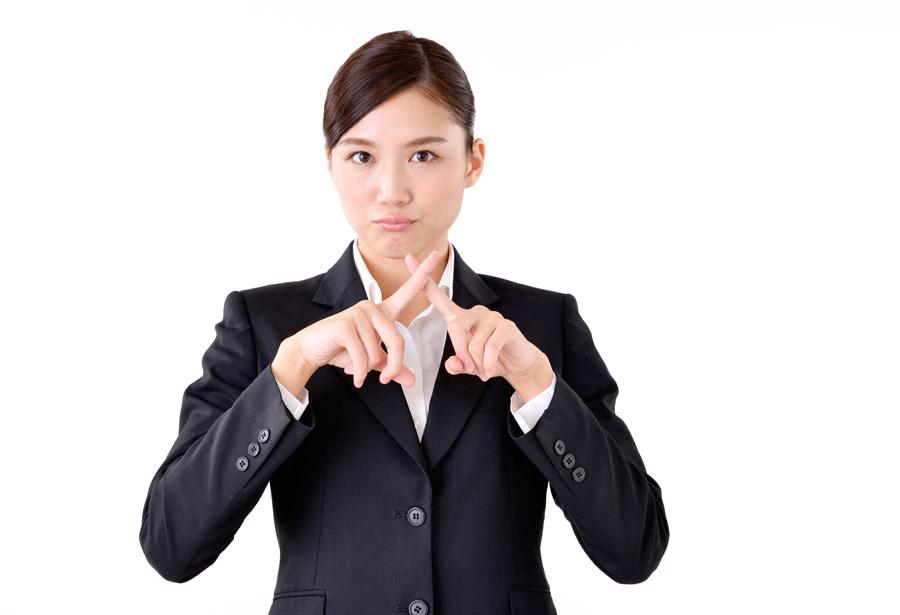 指でバッテンを作る女性会社員