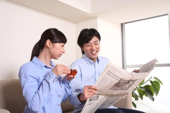 一緒に新聞を読んでいる夫婦