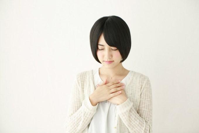 胸に手を当てて心を込める日本人女性