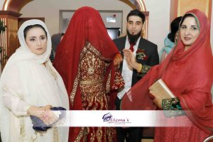 A muslim bride with head covering being escorted by family on Rukhsati