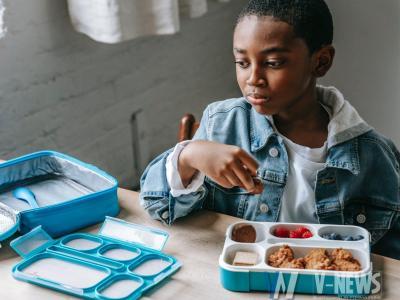 crop dreamy black schoolboy with lunch box in classroom