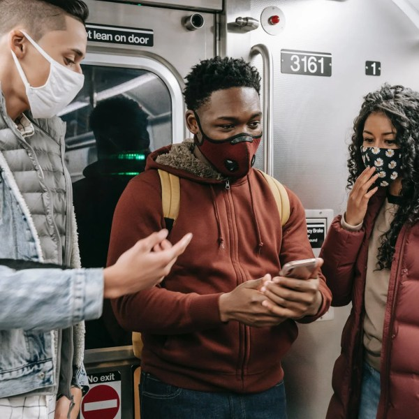 faceless multiethnic students in masks in subway train with phone