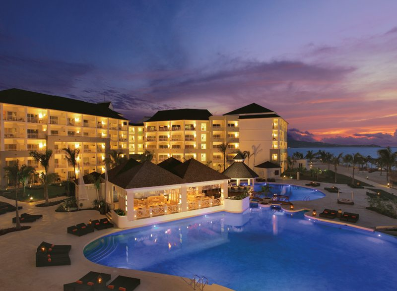 The large, pristine swimming pool at Secrets St. James during the sunset.