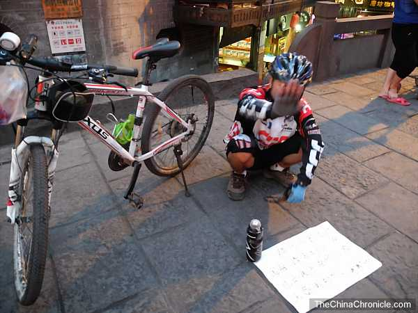 Bicycle traveler begging for travel funds in Fenghuang