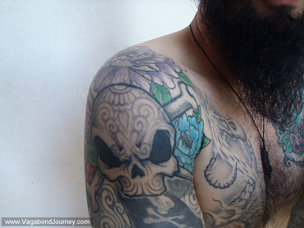 half sleeve of tattooed Mexican sugar skulls that cover her upper arm.