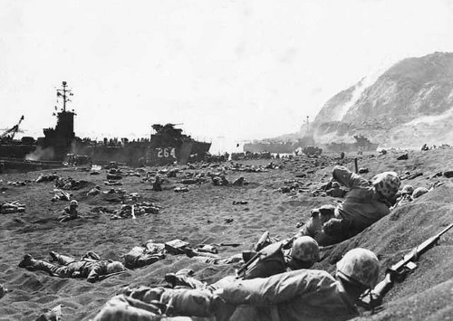 Marines burrow in the volcanic sand on the beach of Iwo Jima, as their comrades unload supplies and equipment from landing vessels despite the heavy rain of artillery fire from enemy positions on Mount Suribachi in the background.