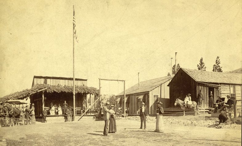 "The Hart mining camp, ""Poverty Flats,"" east of Gilman, Colorado, and just below Bell's Camp on Battle Mountain. A group of adults appear to be playing tennis while children in the background are swinging. Two children are sitting on a pony at far right. At far left, people are seated under a shelter. Buildings are visible in the background"