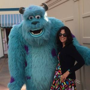 Woman with dark hair and sunglasses standing next to costumed character Sulley from Monsters, Inc.