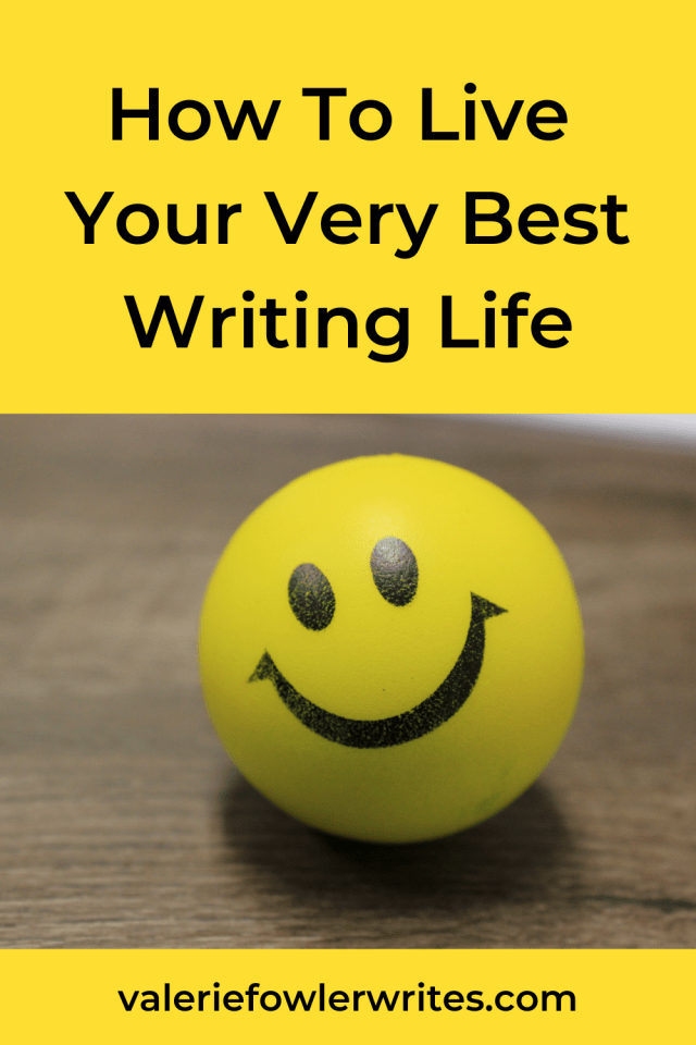 Yellow ball with smiley face sitting on a wooden surface.