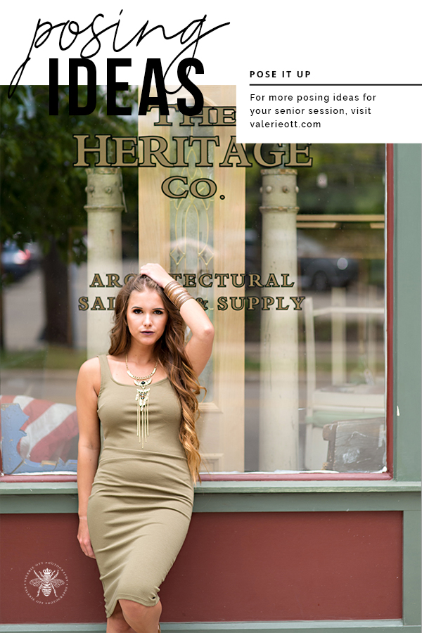 senior girl standing near a store front posing