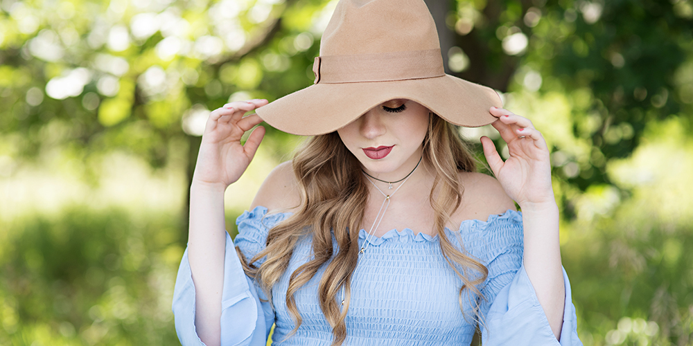 senior girl posing in a field with a hat