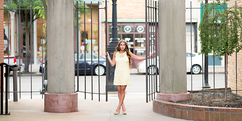 senior girl posing near a gate downtown kalamazoo