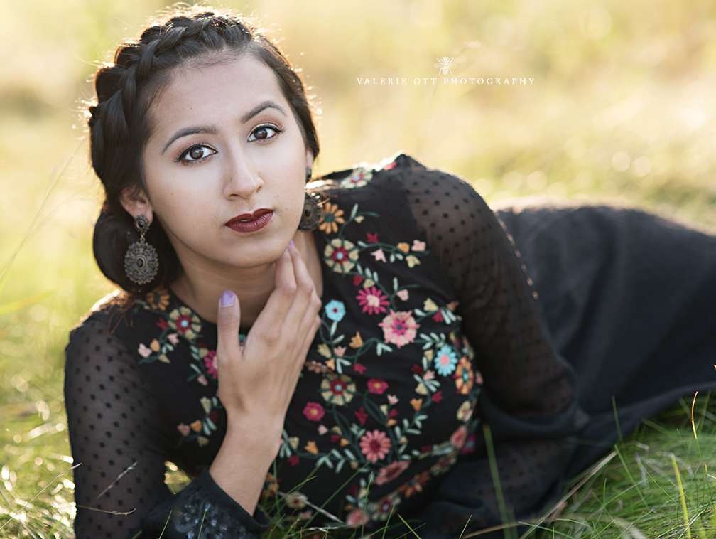 high school girl sitting in a field wearing a black, embroidered dress