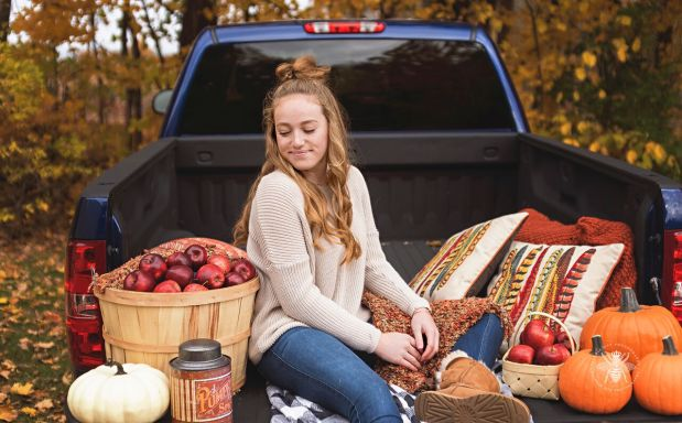 senior girl poses on truck in fall