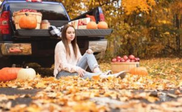 senior girl poses with fall leaves