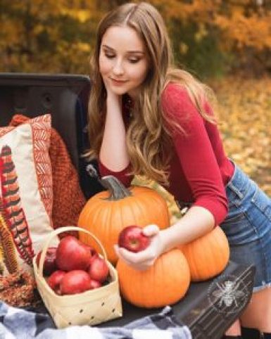 senior girl poses by pumpkins and apples in fall location