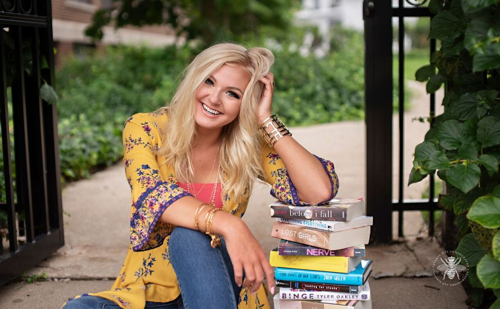 senior girl poses with books