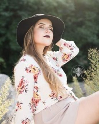 senior girl poses in a hat