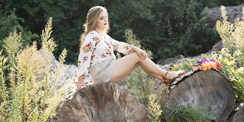 senior girl poses on rocks in floral top