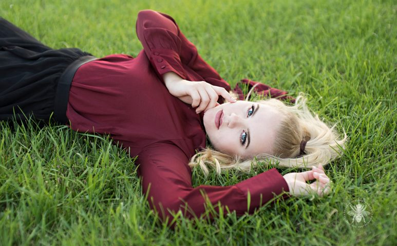 senior girl poses laying in the grass
