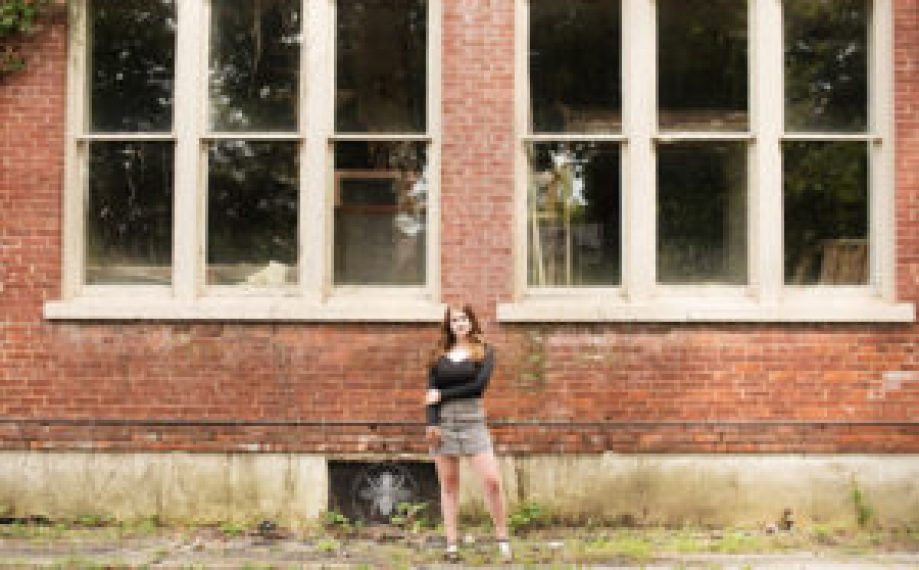 Senior girl poses in black top and a black and white skirt in front of a brick wall.