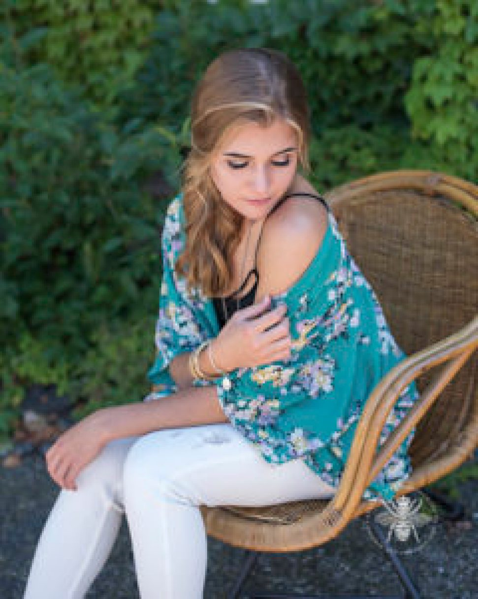 senior girl poses wearing green floral shawl, black tank top, and white jeans