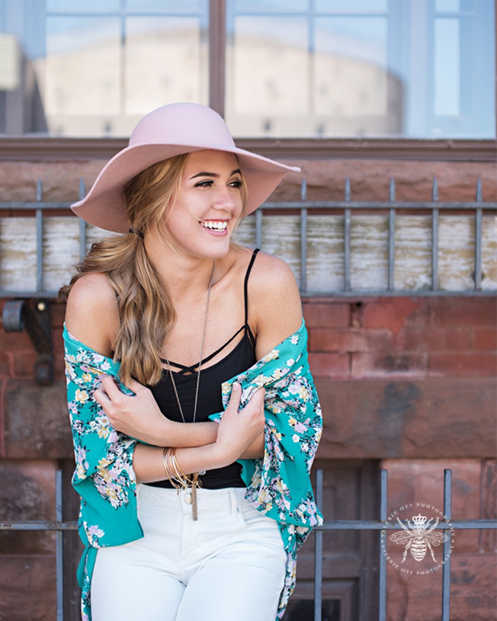 senior girl poses wearing pink hat, green floral shawl, long necklace, black tank top, and white jeans.