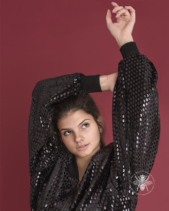 senior girl poses in front of red background wearing a black sequined jacket