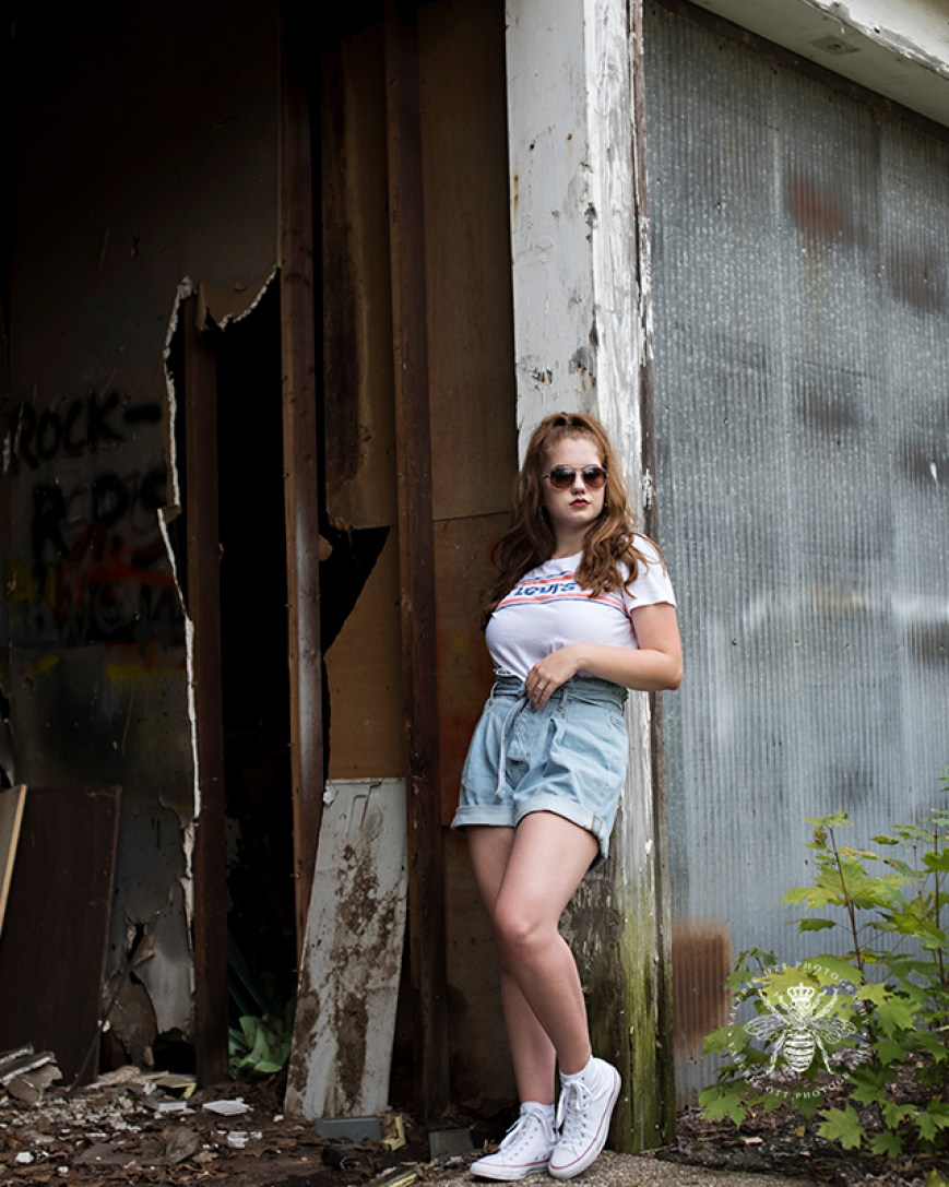 senior girl poses in vintage Levi's top, shorts, and sunglasses