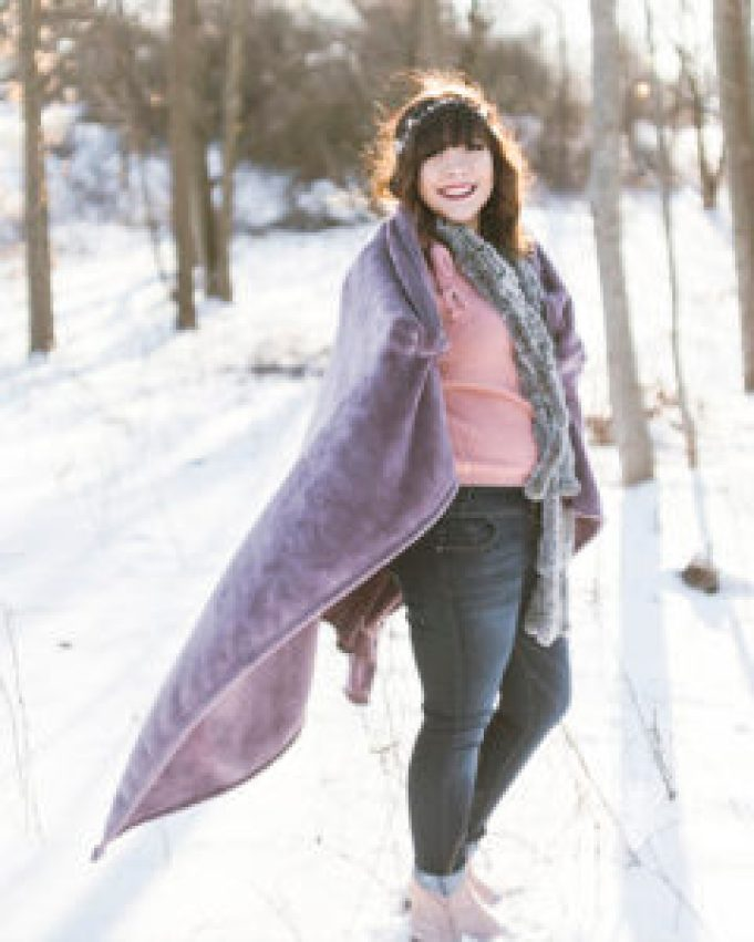 senior girl poses in pink sweater, grey scarf and hat, and purple blanket in winter