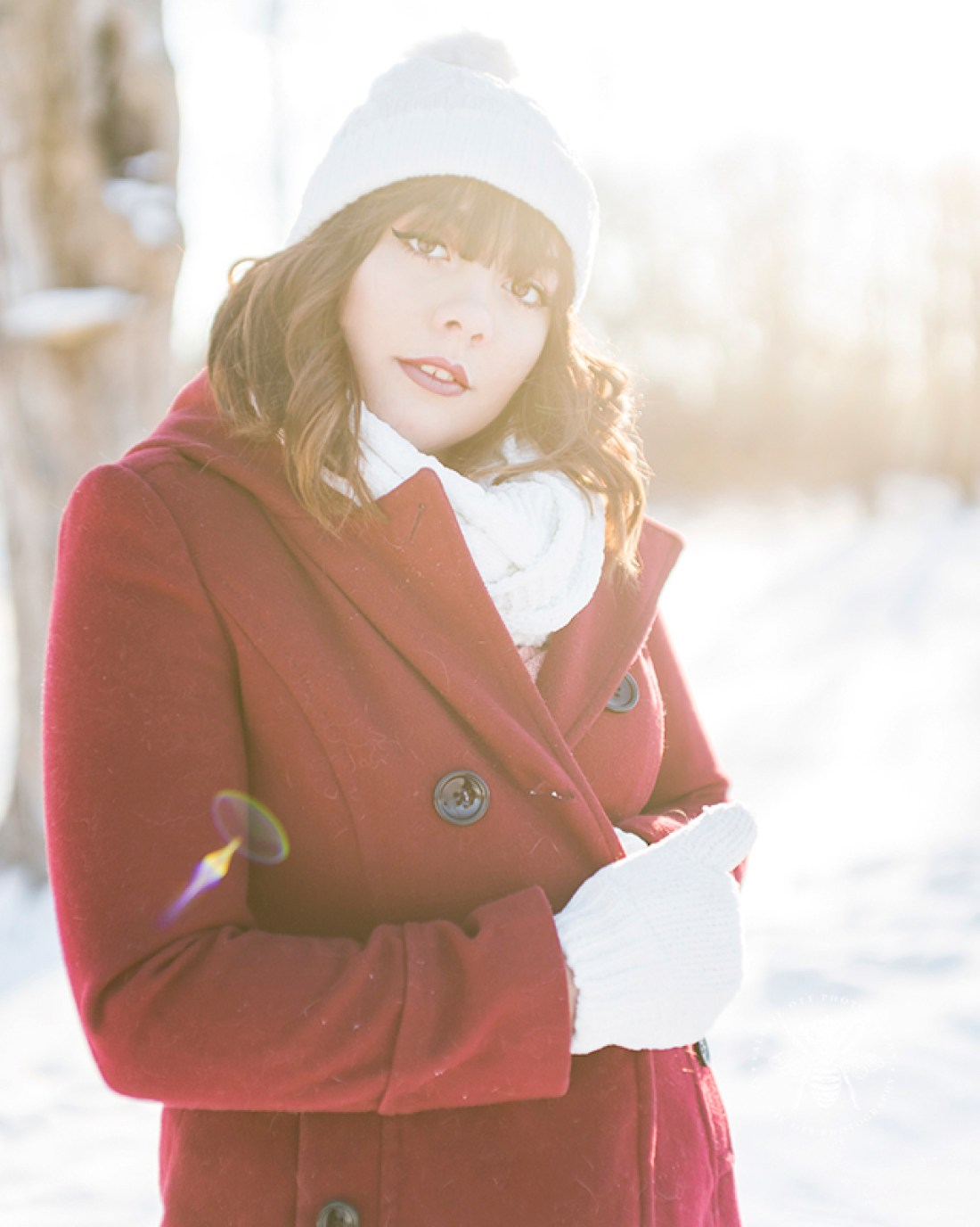 senior girl poses in red coat and white hat, scarf, and gloves in the winter
