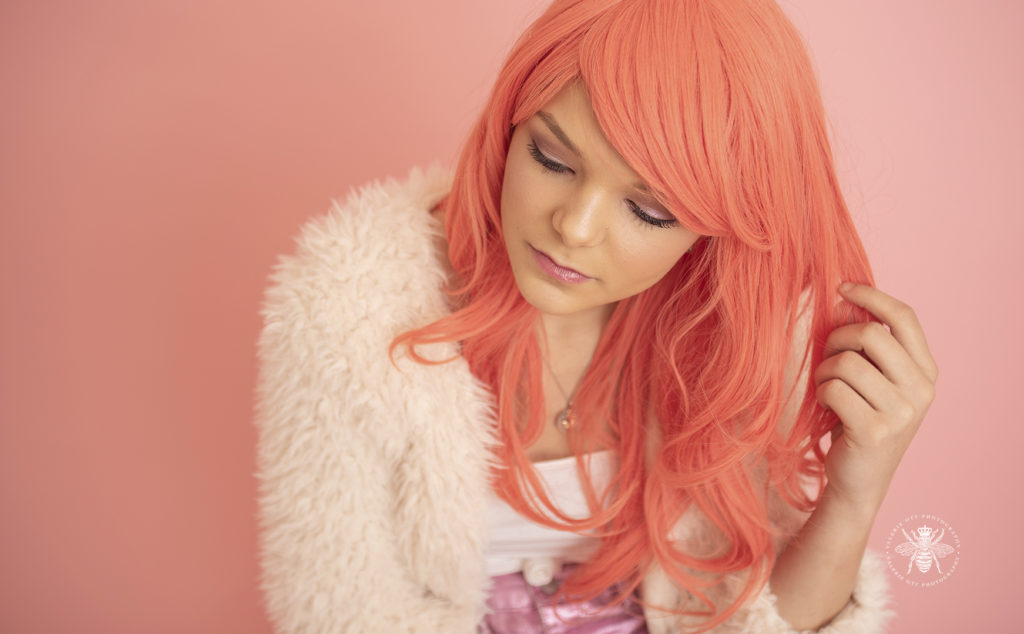 senior girl poses in pink wig in front of pastel pink wall