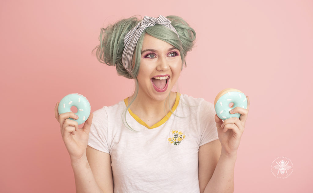 senior girl poses with foam donuts and pastel green colored hair in front of a pink background