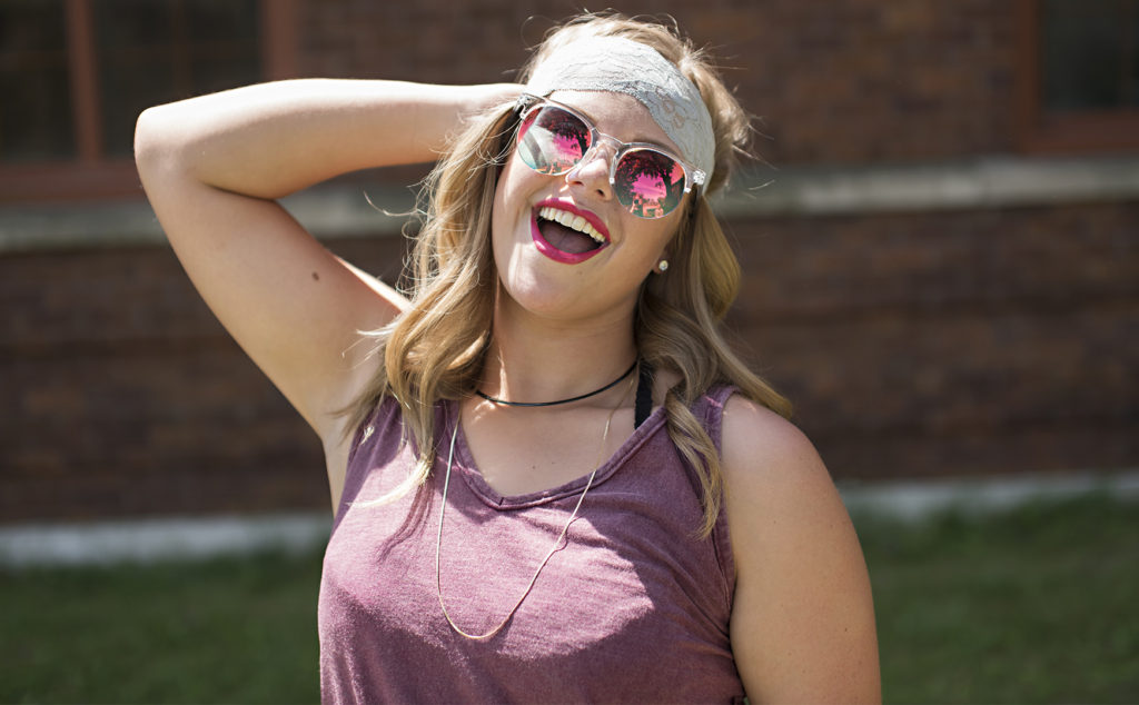 senior girl poses in headband and sunglasses