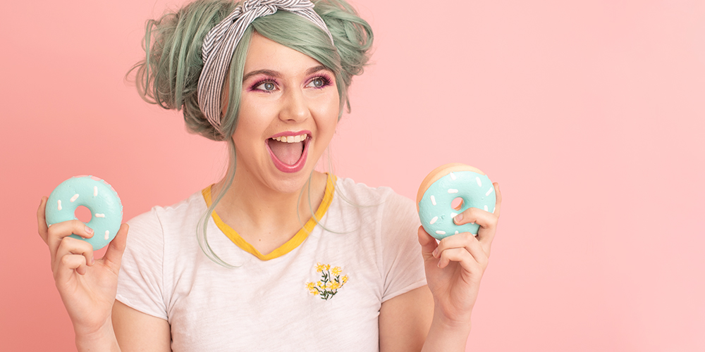 senior girl poses with donuts in front of pastel pink background with green hair