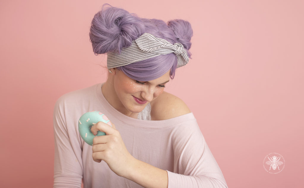 senior girl poses with foam donuts and pastel purple colored hair in front of a pink background